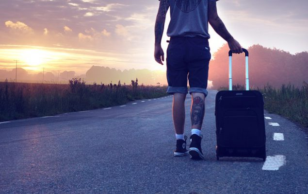 A man with a tattoo on the back of his leg wheeling a suitcase along a road towards a sunset.
