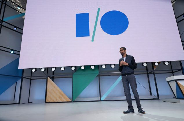 Man standing on stage in front of the Google I/O conference logo, he is probably also being enigmatic