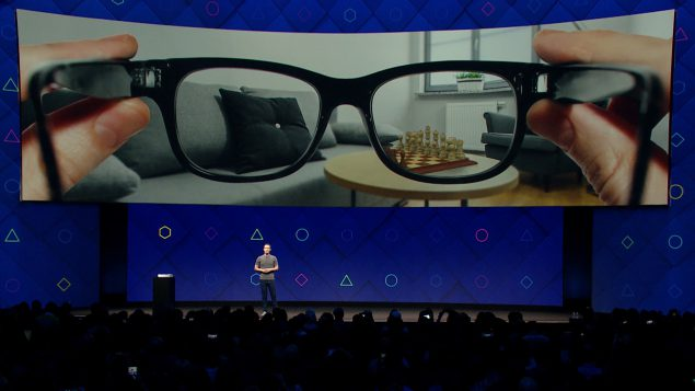 Mark Zuckerberg again looking enigmatic in fron of a screen showing an image of a pair of glasses being held up to the camera with augmented reality chessboard on the table.