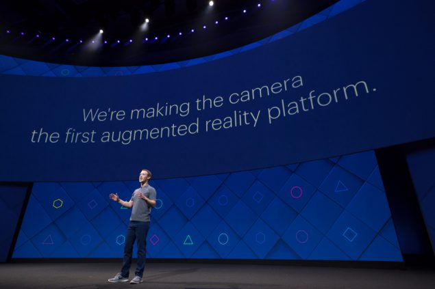 "Mark Zuckerburg standing on stage at the Facebook F8 conference looking enigmatic, in front of a screen with the text ""We're making the camera the first augmented reality platform."""