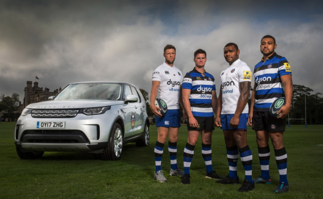 Three Bath Rugby players next to a Land Rover vehicle