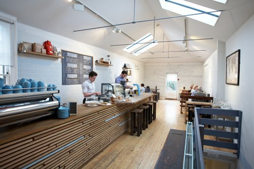 The wooden counter and tables and two baristas in Colonna and Smalls