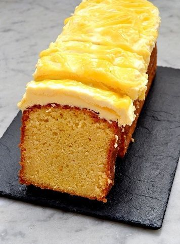 A lemon drizzle loaf with the closest end sliced