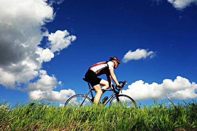 A man cycling next to a green grassy verge with a deep blue sky overhead and dramatic clouds.