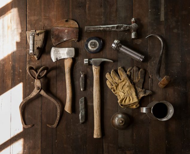 A rustic flat lay of DIY tools such as a hammer, axe, gloves and Stanley knives.