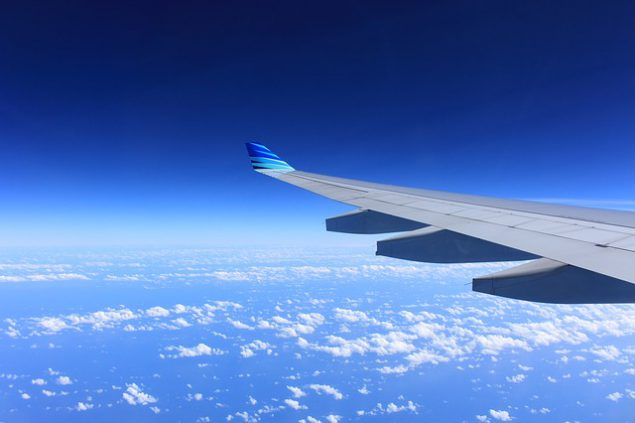 The wing of an aeroplane flying above small whit clouds and a very blue sky