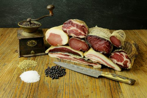 An old fashioned grinder next to various cuts of cured meat and some piled of herbs that are used to cure the meat.