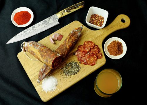 A wooden chopping board with two chorizo sausages on it, surrounded by herbs and spices and a knife