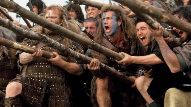 Braveheart and his mates shouting really loudly and holding big sticks